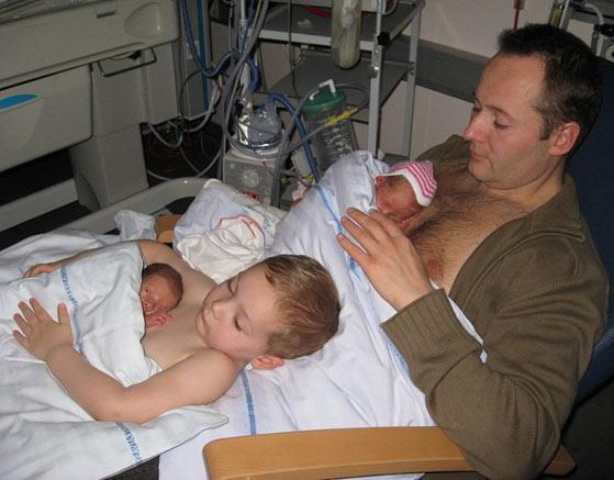 Gêmeos fazendo pele a pele com o pai e com o irmão mais velho